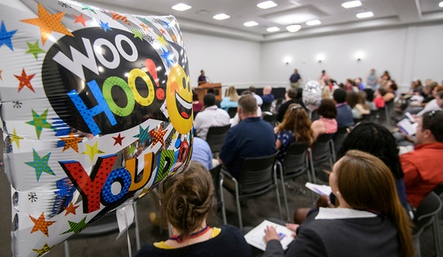 Large room filled with people and a ballon with WooHoo in foreground.